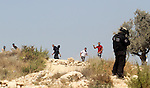 Palestinian protesters throw stones at Israeli border police during clashes after a protest against Israel's separation barrier and in solidarity with Palestinian prisoners being held in Israeli jails, in the West Bank village of Bilin near Ramallah August 30, 2013. Photo by Issam Rimawi