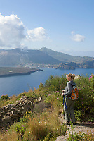 ITA, Italien, Sizilien, Liparischen Inseln, Blick von der Suedspitze der Hauptinsel Lipari auf die Nachbarinsel Vulcano mit dem noch taetigen Krater Gran Cratere, Frau wandert, im Hintergrund ist der Aetna erkennbar | ITA, Italy, Sicily, Aeolian Islands or Lipari Islands, view from main island Lipari at neighbouring island Vulcano with still active crater Gran Cratere, woman hiking, at background vulcano Etna