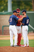 Elizabethton Twins pitching coach Luis Ramirez (19) talks with relief pitcher Austin Schulfer (16) and catcher Trevor Casanova (33) in a mound visit during a game against the Bristol Pirates on July 29, 2018 at Joe O'Brien Field in Elizabethton, Tennessee.  Bristol defeated Elizabethton 7-4.  (Mike Janes/Four Seam Images)