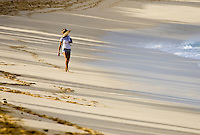 A woman in a sunhat walks the wide open beaches of the North Shore of Oahu.