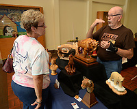 NWA Democrat-Gazette/ANDY SHUPE<br /> Longtime woodcarver and teacher Jim Willis of Kansas City, Mo., (right) speaks Saturday, Sept. 7, with Pam Horstman during the Woodcarvers of NWA Show at Frisco Station Mall in Rogers. The show continues 10 a.m. to 4 p.m. today.