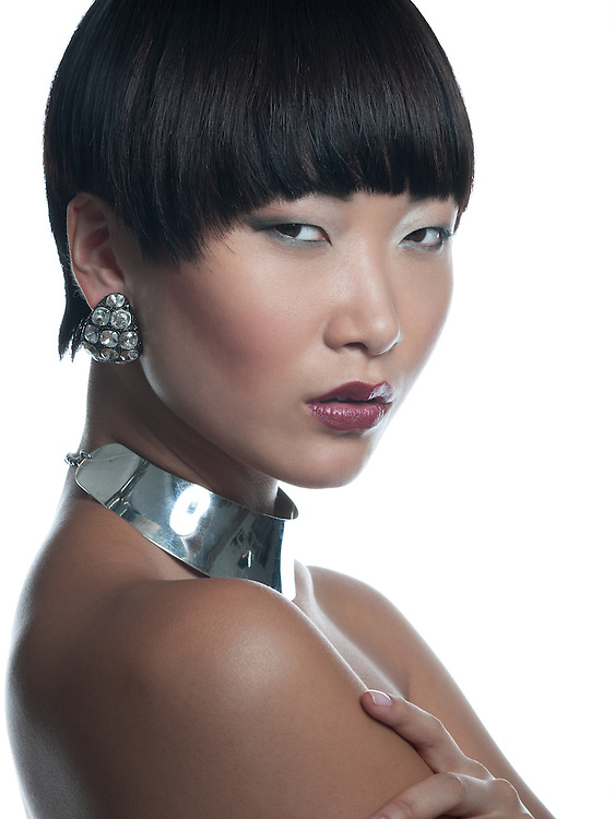 Beautiful asian brunette model in silver necklace & earrings close-up
