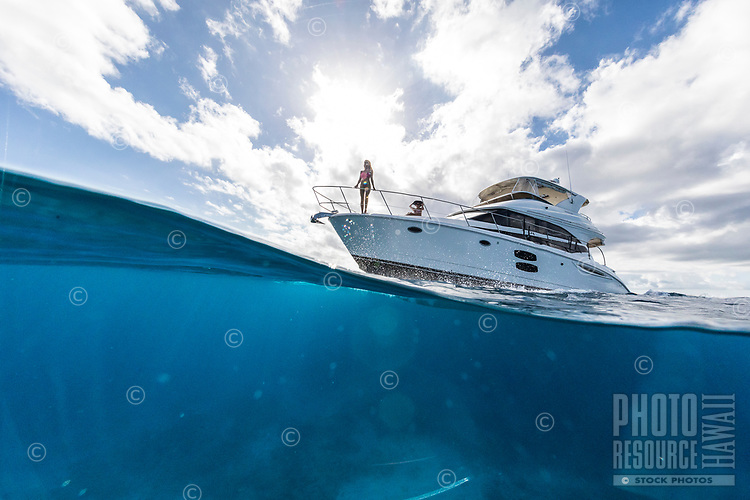 Two women enjoying the view aboard a day cruise in the waters of Waikiki, O'ahu.