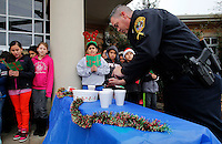 NWA Media/DAVID GOTTSCHALK - 12/18/14 - Steve Linton, officer with the city of Rogers Police Department, adds marshmallows  to a cup of hot chocolate as he listens to fifth grade students at Old Wire Road Elementary School sing while participating in Caroling for Cops Thursday December 18, 2014 at the school in Rogers. The fifth graders  performed Christmas songs, handed out Christmas cards and served hot chocolate during the holiday program.
