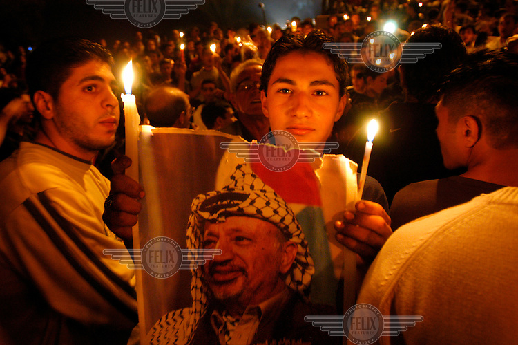Palestinian youths participate in a memorial ceremony to Yasser Arafat near the Damascus Gate of Jerusalem's old city, the day the Palestinian leader's death was declared.