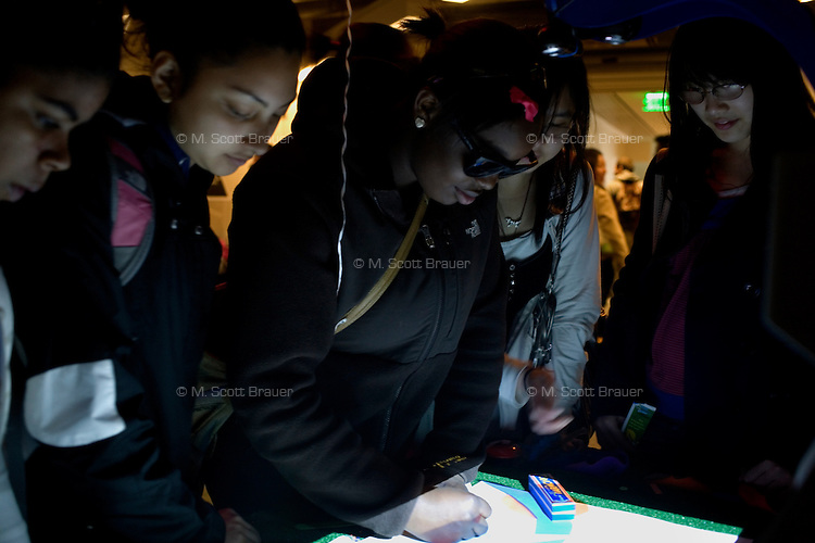 "Visitors play with ""The Neverending Drawing Machine,"" a project by Edwina Portocarrero, research assistant in the Media Lab's Center for Future Storytelling, during the MIT Under the Dome open house in Cambridge, Massachusetts, USA."