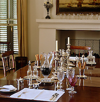 The antique dining table is formally laid with starched table linen and a collection of fine silverware
