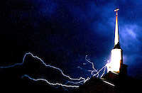 Rick Wilson Photo--7/16/04--Lightning dances creates a spider-web like design in the sky above a church steeple during a Summer thunderstorm.