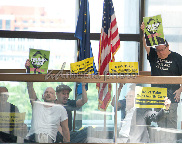 """Protestors chanting """"Healthcare is a right"""" stage a sit-in outside the office of United States Senator Lisa Murkowski (Republican of Alaska) in the Hart Senate Office Building in Washington, DC on Wednesday, June 28, 2017. Photo Credit: Ron Sachs/CNP/AdMedia"""