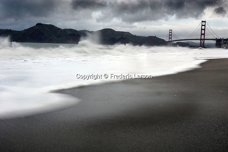 The morning rains stirred up the ocean at Bakers Beach as heavy dark rain clouds moved in over the hills of Marin and the Golden Gate Bridge in San Francisco, California. .