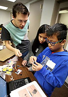 NWA Democrat-Gazette/DAVID GOTTSCHALK  Rex Hearns (from left), an instructor with Modbot, works with Lily and Luu Adler Monday, March 19, 2018 in the Nerdies Spring Break Session Build a Modbot Robot at the NWA Fab Lab in Fayetteville. The three day camp for students ages 9-15 is a partnership between the New Design School and NWA Fab Lab. The students will build, wire, program and then bring the modbot robots home. The students also learned the essentials of soldering and Arduino Programming.