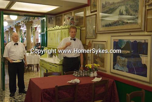 Venice Italy 2009. Interior resturant waiter sampling dinner guests wine./