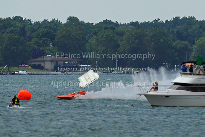 "Frame 5: At the start of the final heat, Kent Henderson, S-00 ""Bank On It""  leads into the first turn when the right side of the boat pulls up and carries the boat into a ""blowover"" flip. The hull spins in the air, comes back to the surface upside down, digs in, and then flips right side up, coming to a rest as CS-79 ""Bad Influence"" races past on the outside. Henderson was uninjured in the accident with slight damage to the boat.  (2.5 Litre Stock hydroplane(s)"