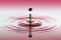 Green water drop falling into red / pink water