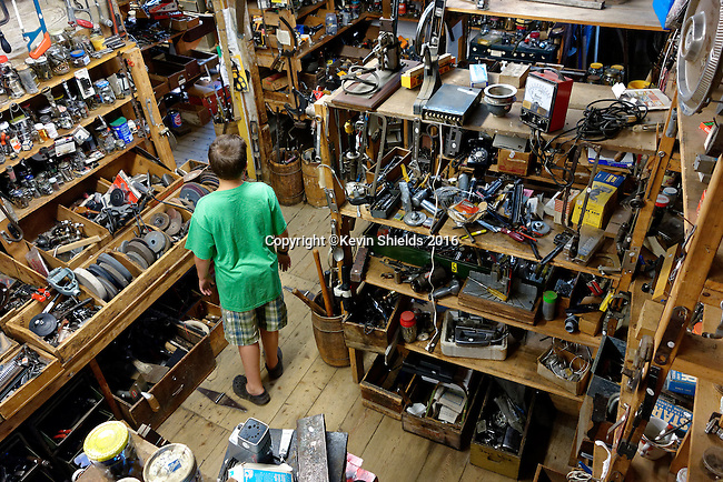 Young man among items for sale at Liberty Tool Company, Liberty, Maine, USA