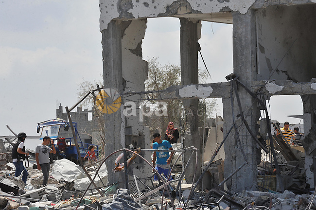 Palestinians walk in front of the rubble of buildings destroyed in Israeli strikes, in Beit Lahiya, northern Gaza Strip, Monday, Aug. 4, 2014.. Photo by Ezz al-Zanoun