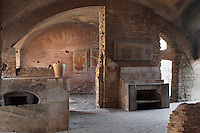 Thermopolium of Via di Diana (Taberna), 3rd century AD, Ostia Antica, Italy. L-shaped counter visible on the left and marble side-table on the right with fresco of food on the wall above. Picture by Manuel Cohen