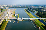 Nederland, Zuid-Holland, Botlek, 28-09-2014; Functioneringssluiting Hartelkering. De waterkering in het Hartelkanaal wordt een maal per jaar, voordat het stormseizoen begint, getest. Tijdens het sluiten van de kering ligt alle scheepvaartverkeer naar de Rotterdamse haven stil.<br /> De kering, onderdeel van de Deltawerken, vormt samen met de Maeslantkering de Europoortkering en beschermt Rotterdam en achterland bij extreme waterstanden.<br /> Port of Rotterdam. Aerial view of one of the two storm surge barriers. This barrier, the Hartelkering in the Hartel canal, is tested once a year together with the greater nearby Maeslant barrier (in the New Waterwy), <br /> During the so-called functioning closure, taking place one a year before the storm season begins, the waterway and canal, leading to the Port of Rotterdam, are closed.<br /> luchtfoto (toeslag op standard tarieven);<br /> aerial photo (additional fee required);<br /> copyright foto/photo Siebe Swart