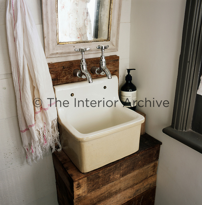 A detail of a simple bathroom where a wooden crate has been used for the sink base.