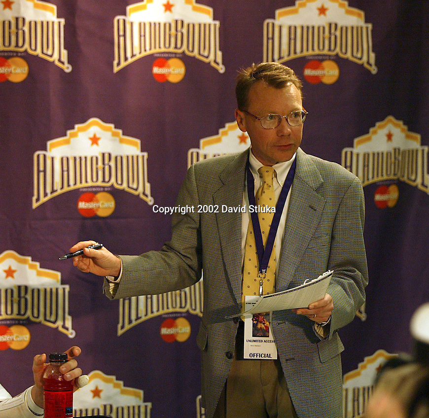 University of Wisconsin associate athletic director Steve Malchow talks with the media at the post-game press conference at the Alamo Bowl in San Antonio, Texas. The Badgers beat the University of Colorado in overtime 31-28 on 12/28/02. (Photo by David Stluka)