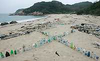 Plastic bottles are arranged into a cross shape on the East-facing beach on the windward side of South Sokos Island, Hong Kong, China, 27 January 2010. South Sokos Island is one of a very small number of uninhabited islands in Hong Kong Special Administrative Region of China, and because it has no ferry service at all it is rarely visited by anyone. Consequently large amounts of marine-borne plastics build-up over time, with infrequent Hong Kong Government pollution clean-up efforts to tackle the problem. Common items found washed up on the beach at South Sokos Island include; lightbulbs, medical waste, plastic bottles, plastic cigarette lighters, plastic toys, plastic fishing equipment and plastic footwear. Another plastic item frequently found in large quantities on Soko Island, but also on polluted beaches the world over, is the pre-production plastic pellet, or 'nurdle', that is used in the manufacturing of plastic products. ALEX HOFFORD