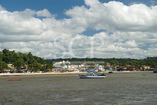 Praia da Concha, Itacare, Bahia State, Brazil. View of teh town across teh bay with a tourist boat.