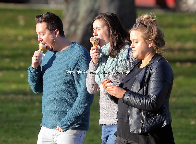 Three young people enjoy an ice cream in the sunny but freezing cold weather, while walking on St Helen's Road in Swansea, Wales, UK
