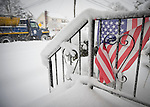 Merrick, New York, U.S. February 13, 2014 - As yet another snow storm slams into Long Island, a snow plow on the road drives past a snowy American Flag decorating the unshoveled front stoop of a home. Gov. Cuomo declared a state of emergency for L.I. and much of the state, and 5 to 14 inches of snow are expected to fall on Nassau and Suffolk Counties through to the evening,