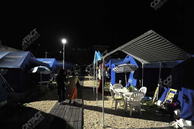 In the camp of piazza d'Armi in L'Aquila, where 1,300 people who lost their homes in the Abruzzo earthquake in April are now living in tents, an elderly woman was  helped back to her tent after dinner. May 22, 2009