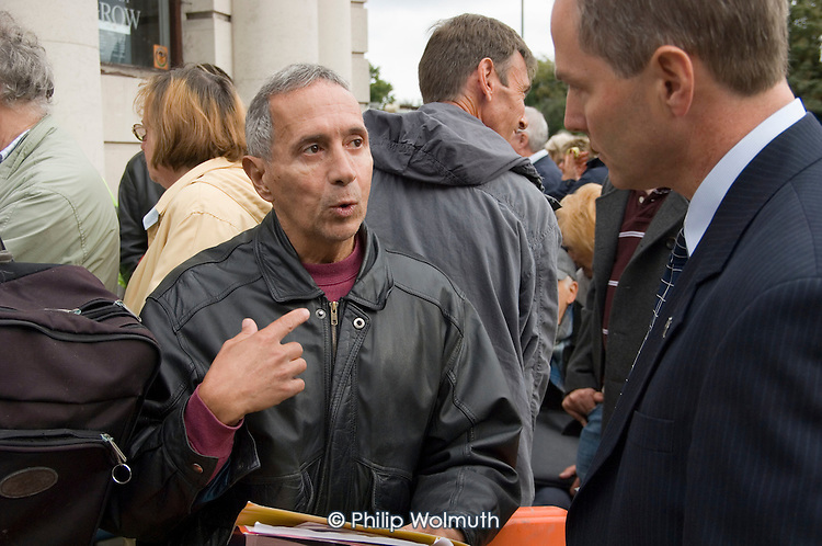 A depositor talks to a Northern Rock manager as savers queue to withdraw their money from a branch of the bank in north London.