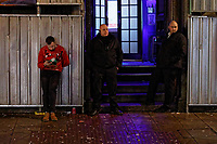 Pictured: A man rests against a fence next to door staff at Idols in Wind Street, Swansea, Wales, UK. Friday 20 December 2019<br /> Re: Black Eye Friday (also known as Black Friday, Mad Friday, Frantic Friday) the last Friday before Christmas, in Swansea, Wales, UK.