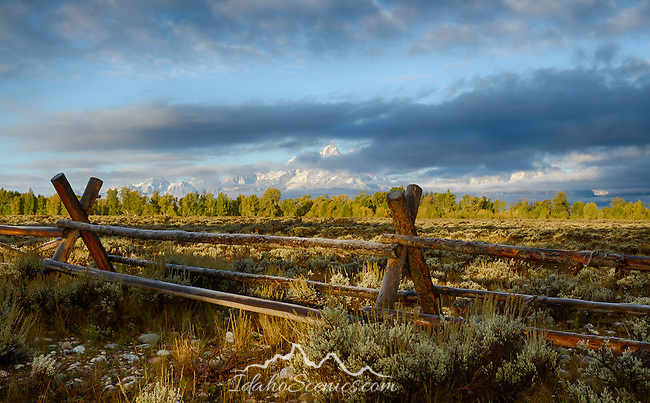 Wyoming, GTNP, Grand Teton National Park, morning sun lights the landscape including the Teton Range partially obscurred by low clouds.
