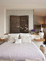 A low wall behind a double bed acts as a headboard, which separates a dressing room from a bedroom. Two floating shelves act as bedside tables upon which are placed golden lamps from Pierre Cardin.