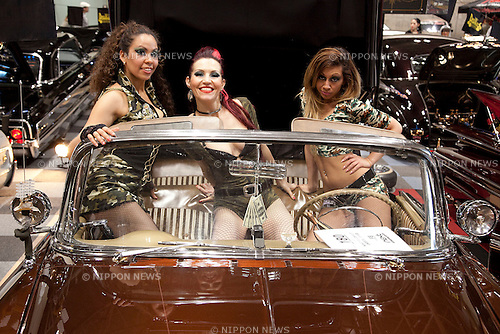"""April 21, 2013, Chiba, Japan - Go-Go dancers pose for the camera on the customer car. The """"New Style Custom Autoshow NEXT 2013"""" for 5th time comes to Makuhari Messe to show luxury custom cars (Lamborghini, Maserati, Cadillac, Honda, Chevrolet, etc) which compete in 16 different """"New Style"""" categories. The exhibition brings beautiful Go-Go dancers who perform on the stage and pose for the cameras of visitors. The car show brings the ultimate of technology in illumination, audio and video system; car accessories, rims and new designs on chassis, everything to custom luxury cars. (Photo by Rodrigo Reyes Marin/AFLO).."""