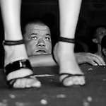 Bao-Jhong Yi-min Temple, Kaohsiung -- Spectator looking up a pole dancer's legs at the annual 'Divine Pig' (Shen Zhu) festival during Ghost Month.