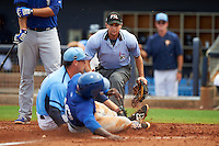 Umpire Joe George watches Anthony Alford (10) slide into home as pitcher Kyle McKenzie (27) applies the tag for the out during a game between the Dunedin Blue Jays and Charlotte Stone Crabs on July 26, 2015 at Charlotte Sports Park in Port Charlotte, Florida.  Charlotte defeated Dunedin 2-1 in ten innings.  (Mike Janes/Four Seam Images)
