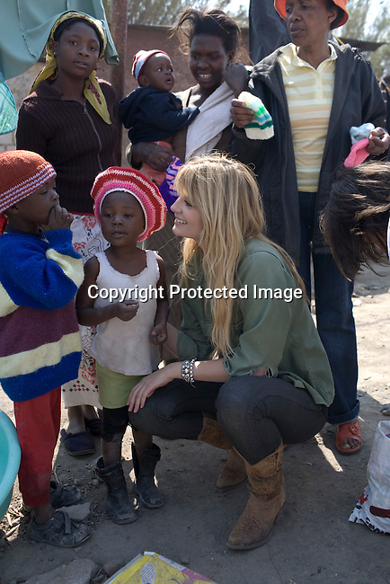 ALEXANDRA, SOUTH AFRICA - SEPTEMBER 2: Mischa Barton, the actress and model, interacts with mothers and children at Hlayisanani Pre-School on September 2, 2008 in Alexandra, outside Johannesburg, South Africa. Mischa Barton spent 2 days visiting Save The Children supported projects in South Africa, meeting school children and young children. Save The Children are helping about 51,000 children made by HIV/AIDS and poverty to access food, healthcare, social security and education. (Photo by Per-Anders Pettersson/Getty Images For Save The Children).