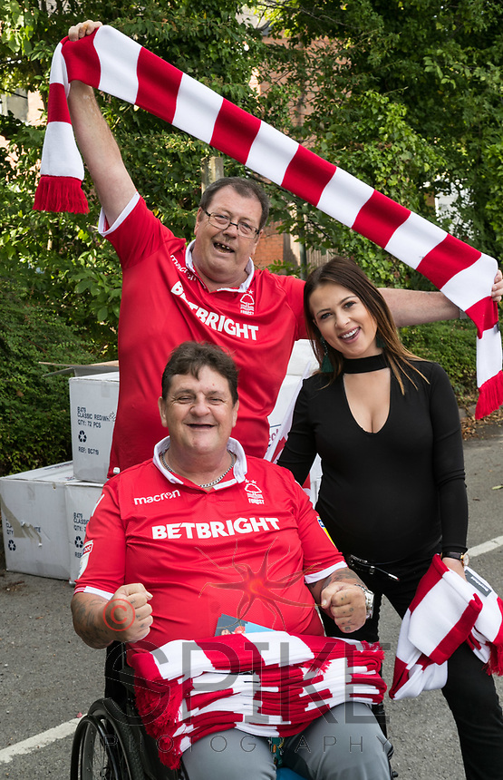 Forest fans John Mollison (standing) and Tony Griffiths of Newark show off their new scarves with Emma Merchant