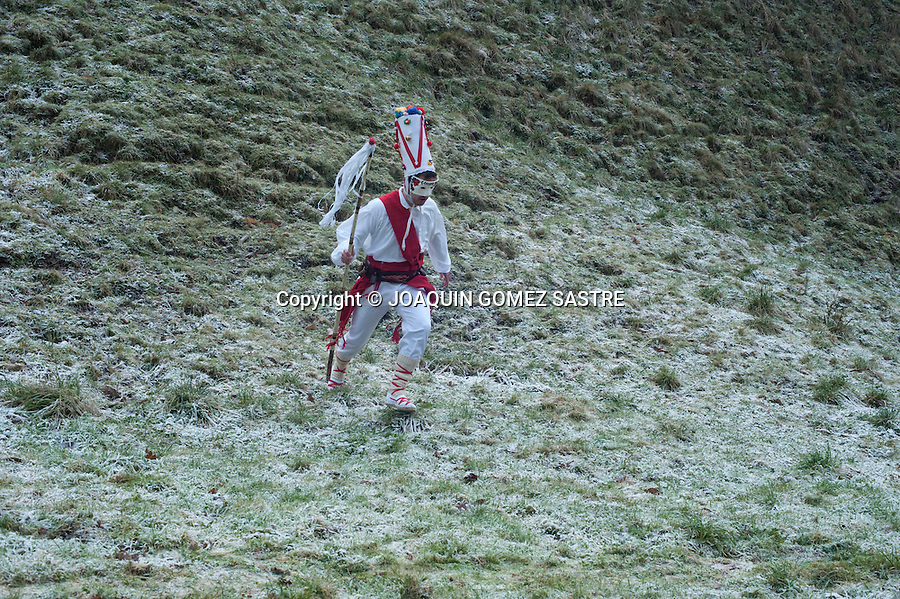 A white dancer descends by a hillside jumping during the first carnival of the year in Silio in the province of Cantabria in the festival of the vijanera.