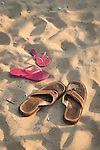 Sandals and togs in sand.