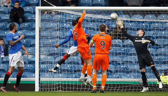 Gavin Gunning rises to beat Maurice Edu in the air to head past Allan McGregor and score for Dundee Utd
