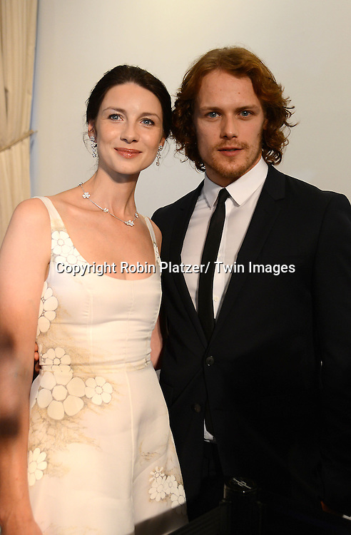 "actress Caitriona Balfe in Honor white dress and Sam Heughan attend the STARZ and Time Warner Cable Screening of ""Outlander"" at the 92nd Street Y on July 28, 2014 in New York City. The Network's New Orginal scripted drama will debut on August 9, 2014."
