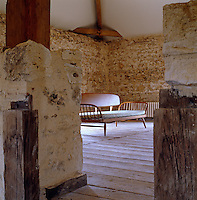 An Ercol daybed is glimpsed through two pillars in the converted granary