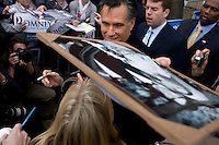 Former Massachusetts governor Mitt Romney hands back a wedding picture brought by a supporter after he signed it after a town hall meeting and rally at the Rochester Opera House in Rochester, New Hampshire, on Jan. 8, 2012. Romney is seeking the 2012 Republican presidential nomination.