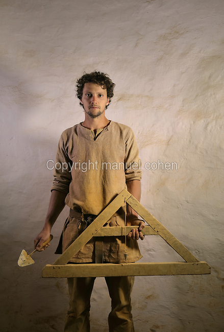 Baptiste Fabre, bricklayer on the Guedelon project since01/04/2014, wearing medieval costume and holding a trowel and A-frame plumb line, at the Chateau de Guedelon, a castle built since 1997 using only medieval materials and processes, in Treigny, Yonne, Burgundy, France. The Guedelon project was begun in 1997 by Michel Guyot, owner of the nearby Chateau de Saint-Fargeau, with architect Jacques Moulin. It is an educational and scientific project with the aim of understanding medieval building techniques and the chateau should be completed in the 2020s. Picture by Manuel Cohen