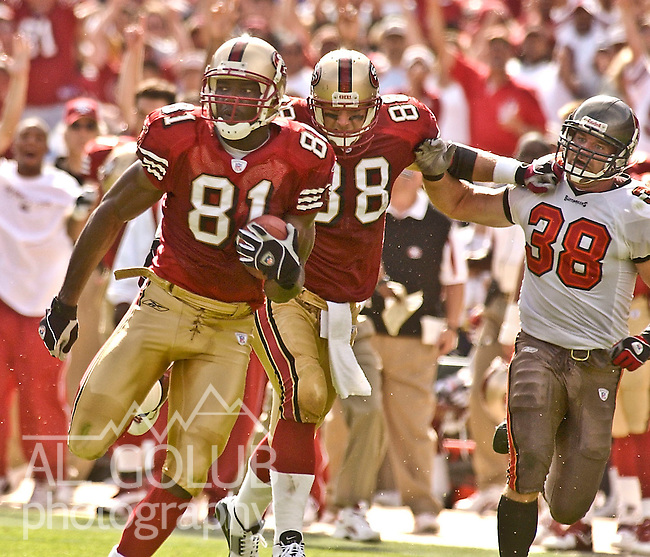 San Francisco 49ers wide receiver Terrell Owens (81) make big run as  tight end Jed Weaver (88) holds off Tampa Bay Buccaneers defensive back John Howell (38) on Sunday, October 19, 2003, in San Francisco, California. The 49ers defeated the Buccaneers 24-7.