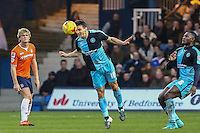 Matthew Bloomfield of Wycombe Wanderers (centre) wins the ball as Cameron McGeehan of Luton Town (left) and Aaron Pierre of Wycombe Wanderers (right) look on during the Sky Bet League 2 match between Luton Town and Wycombe Wanderers at Kenilworth Road, Luton, England on 26 December 2015. Photo by David Horn.