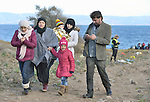 A Syrian refugee family walks near a beach outside of Molyvos, on the Greek island of Lesbos, shortly after they landed there on October 30, 2015. The refugees came on a boat from Turkey, where they paid Turkish traffickers huge sums for the transportation.