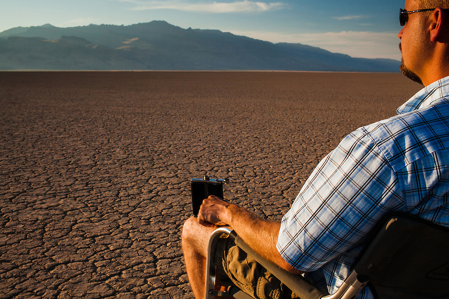 A man in his 30's sits on a Coleman folding chair in the Alvord Desert, looking toward the sunset and Steens Mountain in a remote part of Southeast Oregon.