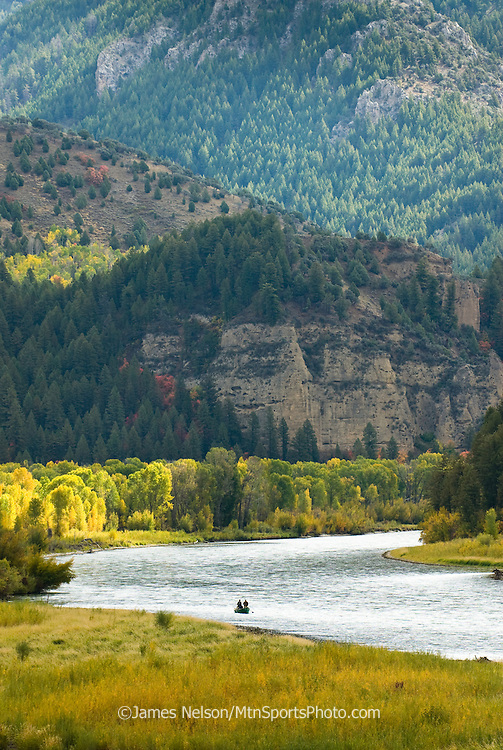 Fly fishers in a drift boat anchor along a bank during a September day on the South Fork of the Snake River, Idaho.